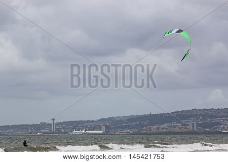 kitesurfer riding his board in Swansea Bay