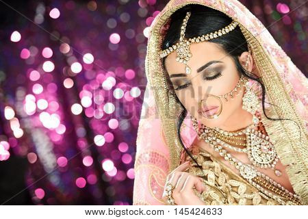 A pretty young female model wearing traditional indian pakistani bridal outfit with heavy jewelry and makeup