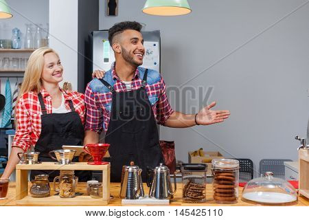 Barista coffee shop owner couple happy smile welcome at bar counter mix race man woman small business
