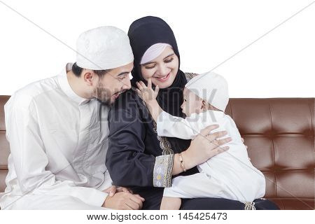 Photo of happy Arabic family joking together while sitting on the sofa isolated on white background