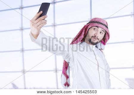 Arabian businessman wearing turban using mobile phone to take picture of himself in office