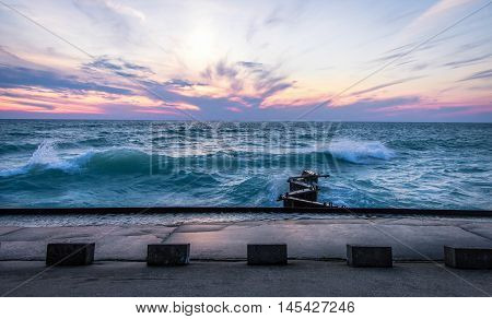 Waves And Lake Michigan Sunset. The sunset over the coast of the Lake Michigan horizon during a gale warning. Lake Michigan is the third largest of the Great Lakes.