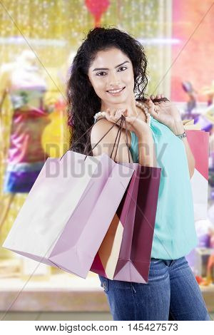 Beautiful female shopaholic smiling at the camera while carrying shopping bags in the shopping center