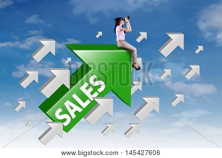 Young businesswoman looking through binocular while sitting on the rising arrow with sales word