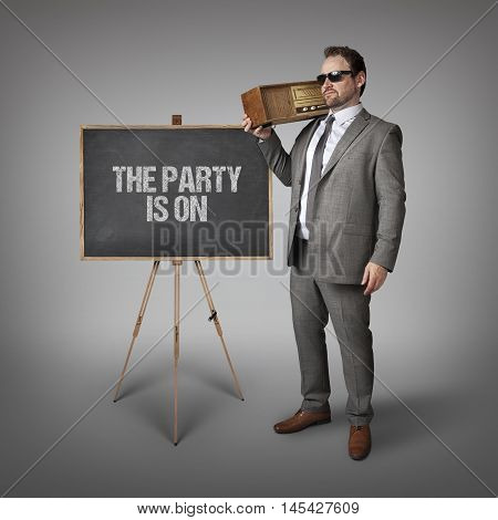 The party is on text on blackboard with businessman holding radio