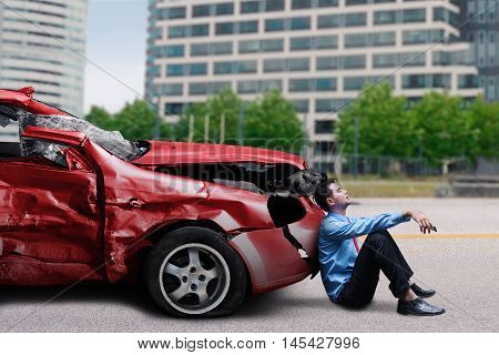 Young man sitting in front of a damaged car while waiting help after collision on the road