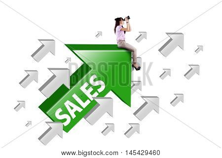 Photo of a young female entrepreneur sitting on the upward arrow with sales word and looking through binocular
