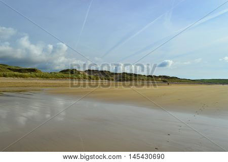 Dramatic cloudscape with contrails over Freshwater West Beach Pembrokeshire