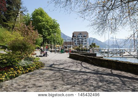 Weggis Switzerland - May 05 2016: Promenade along the shore of Lake Lucerne is the perfect place to spend time and enjoy the beauty of nature. Several people can be seen in a distance. Weggis it is the small holiday resort placed on the shore of Lake Luce