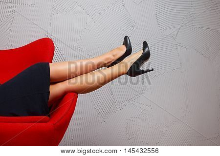woman with long legs resting in a red armchair. beautiful female legs in high heels lying on the armrest of the chair. the concept of leisure, rest and relaxation in the office. empty space for your text