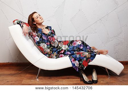 romantic girl lays down on the sofa. young girl in a long flowered dress thoughtfully sitting on the couch. empty space for your text