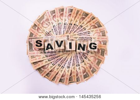 indian currency notes arranged in circular shape and Saving text written on wooden blocks