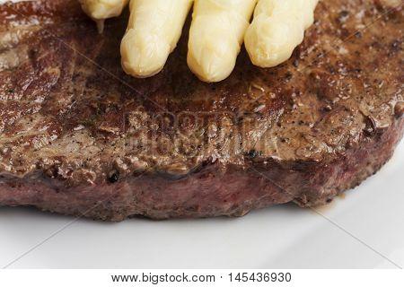 closeup of white asparagus on a steak