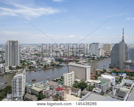 Cityscape and modern building near Chao Phraya River river in the afternoon at Bangkok Thailand under blue sky and cloud
