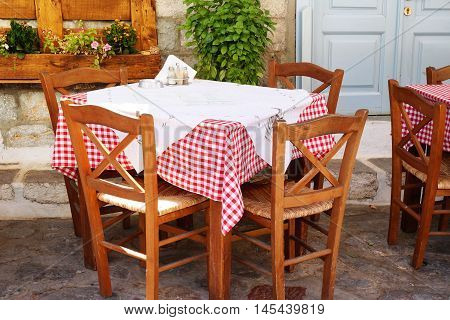 Traditional Greek Tavern Table Covered in Red and White Gingham Checkered Tablecloth