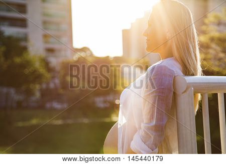 Beautiful Pregnant Woman In A Sunset Outside In The Park