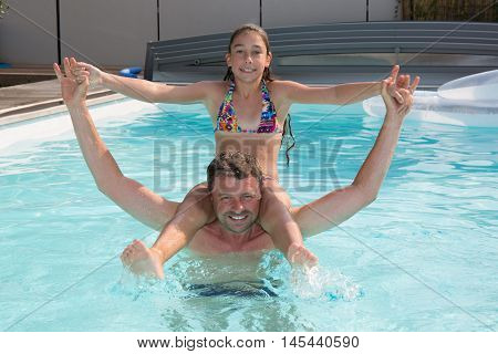 Young girl sitting on father's shoulders in swimming pool