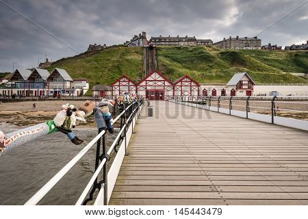 Saltburn Pier and town beyond, at Saltburn by the Sea which is a Victorian seaside resort with a pier and cliff lifts or funicular. The pier gets mysteriously yarnbombed with knitted items