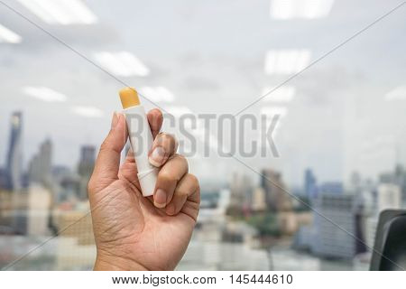 woman hold a lip balm in hand