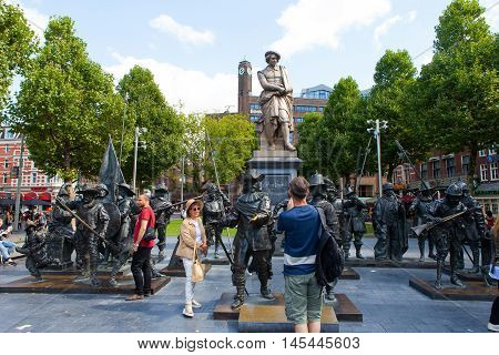 Amsterdam, The Netherlands - August 29, 2016: Sculpture of the dutch painter Rembrandt with and installation of Night watch sculptures on a sunny day in Amsterdam