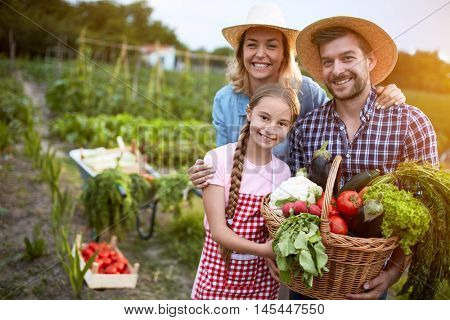 Satisfied farmers family with organic vegetables from garden