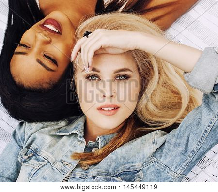 two young pretty teenager girls best friends laying on grass making selfie photo having fun, lifestyle happy people concept, students at summer close up
