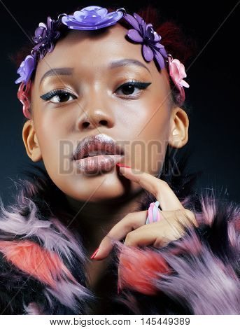 young pretty african american woman in spotted fur coat and flowers jewelry on head smiling sweet etnic make up bright fashion look