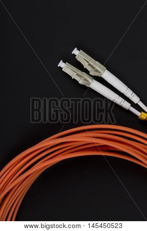 Fiber optic patchcord LC isolated on dark background.