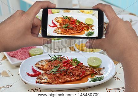 Take photo a dish of mackerel fish fried topped spicy curry with side dish to share for social network.Selective focus.