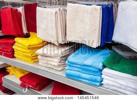 Big pile of colorful towels at shelf