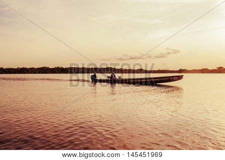 Indigenous People On Typical Canoe Navigating On Lagoon Grande South America