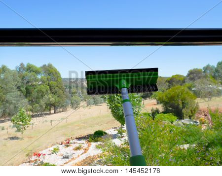 Window squeegee wiping glass on balcony with garden background