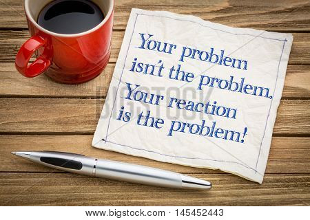 your problem is not the problem. Your reaction is the problem. Inspirational handwriting on a napkin with a cup of coffee.
