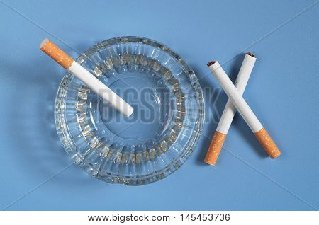 Glass ashtray with cigarette on blue table top view