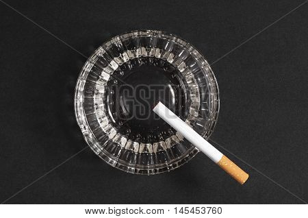 Cigarette and ashtray on a black background top view
