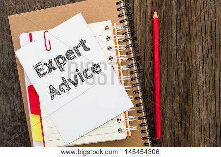 Expert advice, Text message on white paper with notebook on wooden table, top view. business concept