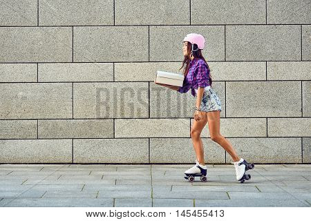 Fast delivery of sportive girl on roller skates. Young woman on roller skates with box or pizza in hands.
