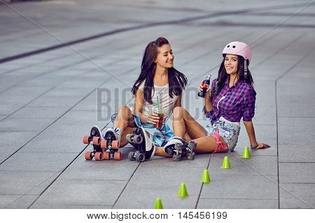 Two girlfriends beautiful women rest after outdoor activities. Happy girls on roller skates resting and drinking lemonade sitting on street a sunny day.