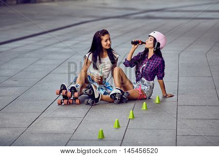 Lifestyle shot of two girl in roller skates having fun in urban skate park. Beautiful hipster girls in roller skates resting and drinking lemonade.