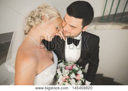 Portrait of happy newly wedding couple with bouquet.