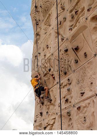 young girl climbing wall at outdoor fair