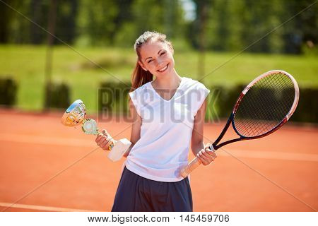 Young female winner in tennis match holding goblet on tennis court
