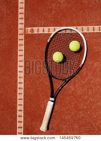 Close up of tennis racket and yellow balls at red clay on tennis court