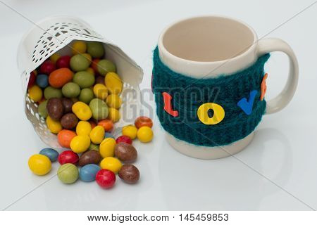 Colorful candy in a pot on a white background with cup holders at