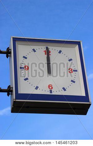 Street Clock Showing Noon On Blue Sky