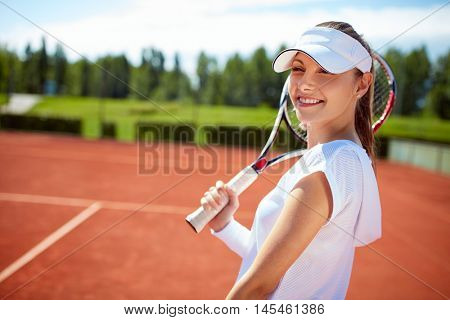 Satisfied girl on tennis court with racket