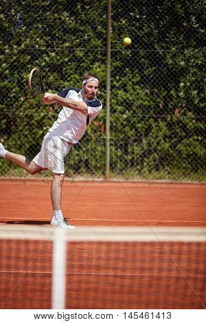 Tennis player in action hitting tennis ball