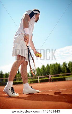 Sportsman playâ??s tennis in tennis court