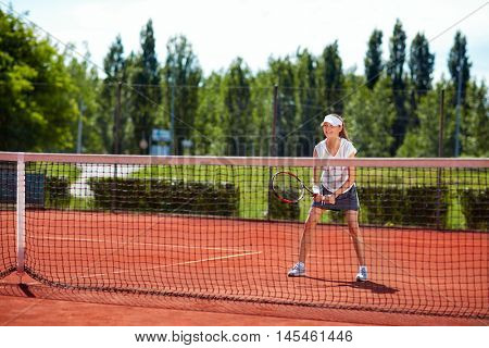 Young girl on tennis training in nature