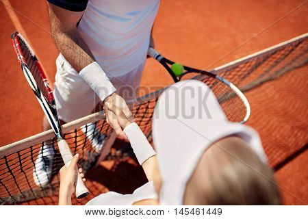 Close up of shaking hands on tennis court after match